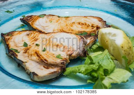A Swordfish Dishes Pics, Among Lemons Cut, On A Glass Dish, Over A Bed Of Lettuce.