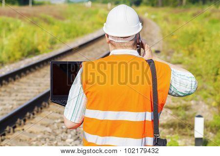 Railway Engineer using smartphone and laptop on railway