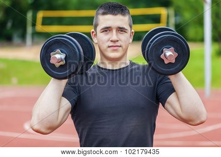 Teenager with dumbbells on sports ground