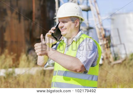 Engineer showing thumb up near to the tanks