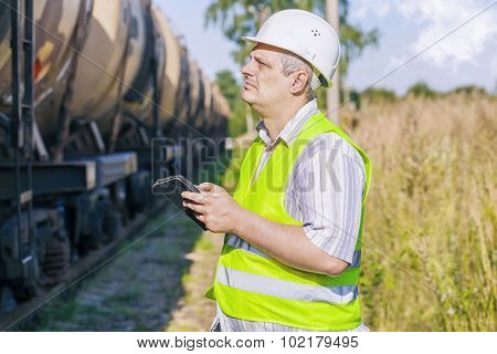 Railway Engineer using tablet PC on railway near freight wagons