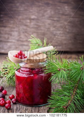 Fresh homemade cranberry sauce in a glass on dark wooden background