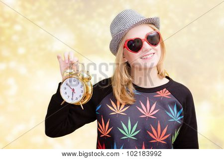 Young woman in sunglasses and fedora hat holding vintage clock