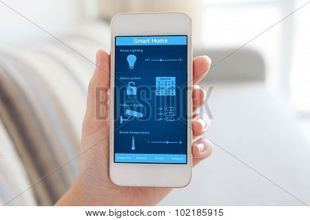 Female Hand Holding Phone With Smart Home On The Screen
