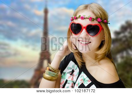 Girl in heart shaped sunglasses on blurred Eiffel tower background