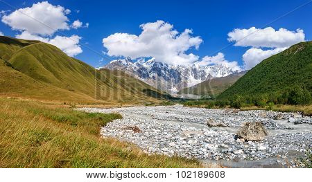 Summer Landscape With River And Mountain Snow.