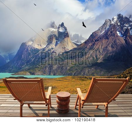 Pleasant holiday in Chile. Wooden chairs in the park Torres del Paine. On the horizon is visible snow-covered rocky mountain