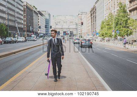Young Handsome Asian Model Walking With His Skateboard