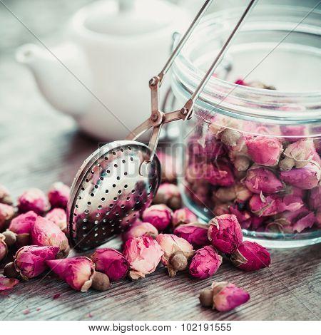 Rose Buds Tea, Tea Infuser, Glass Jar And Teapot On Background. Selective Focus.