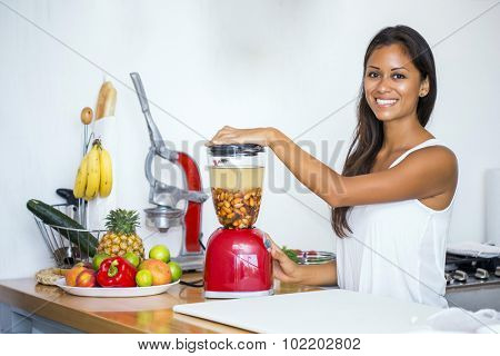 Woman ready to blend a cup of almonds, three dates and three cups of water to make almond milk. Add a pinch of salt and cinnamon and enjoy it fresh.
