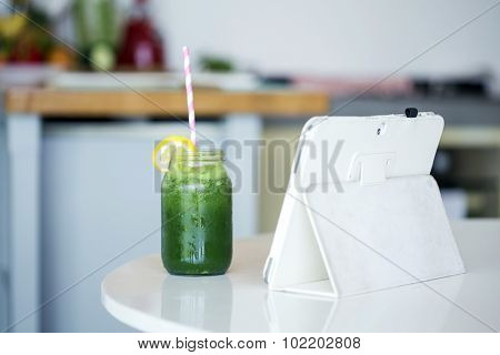 Homemade green detox juice next to a white tablet on a kitchen table