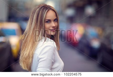Close-up portrait of a beautiful charming blonde girl looking behind and smiling towards the viewer.