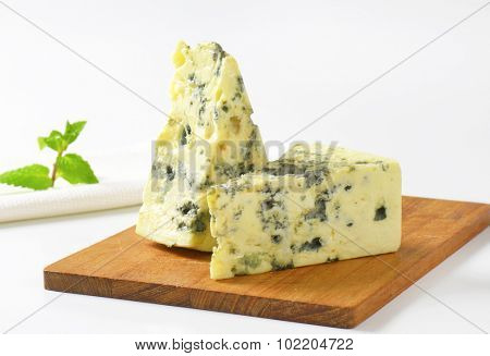 Two wedges of French blue cheese on cutting board