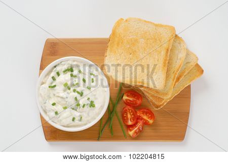 stack of fresh toasts and bowl of chives spread on wooden cutting board
