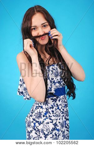 A Portrait Of A Young Girl Holding Hair Mustache To Her Face