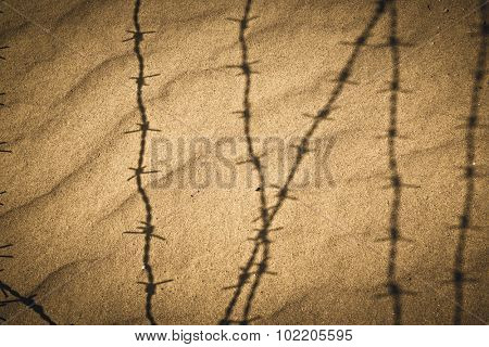 Shadow of metal barbed wire fence on the sand. Concept 'freedom'.