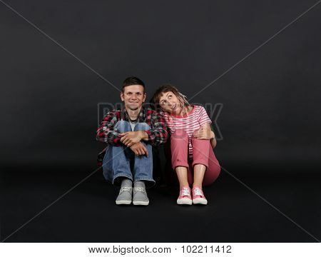 Emotional young couple on black background