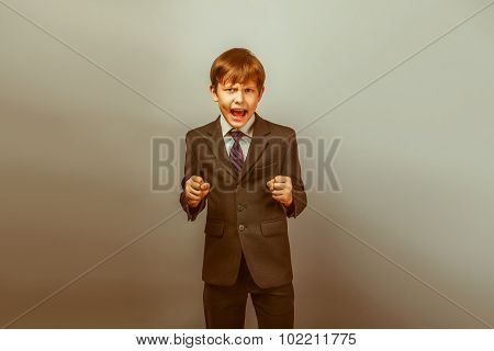 a boy of twelve European appearance in a suit shouting angry on
