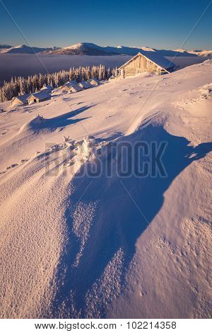 Winter in the mountain village. Landscape with snow drifts