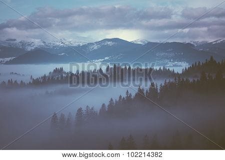Winter Morning with fog in the mountains. Color toning. Low contrast