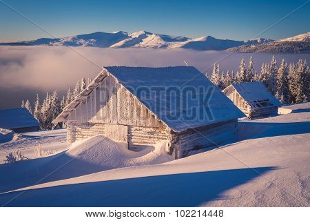 Winter landscape with wooden house in the frost. Mountain village of shepherds. Carpathians, Ukraine, Europe