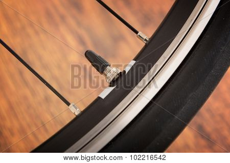 Bicycle tyre valve on the wooden floor