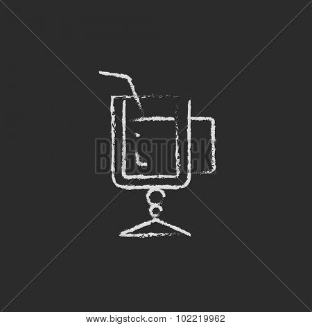 Glass with drinking straw hand drawn in chalk on a blackboard vector white icon isolated on a black background.