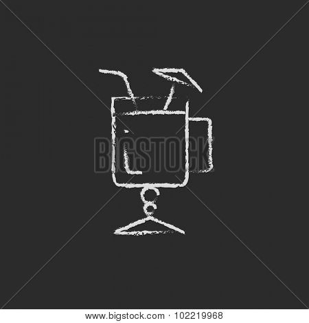 Glass with drinking straw and umbrella hand drawn in chalk on a blackboard vector white icon isolated on a black background.