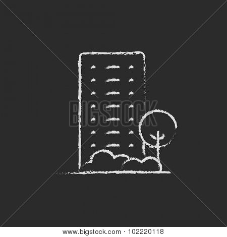 Residential building with trees hand drawn in chalk on a blackboard vector white icon isolated on a black background.