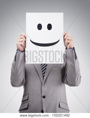 Businessman holding and hiding behind a card with smiley face emoticon