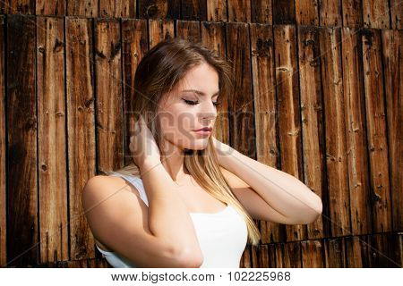Woman breathing deep with wooden planks in a background