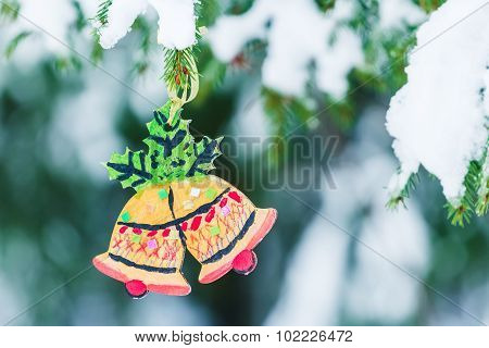 Handcrafted wooden ornament of Christmas Bells hanging on snowy spruce tree