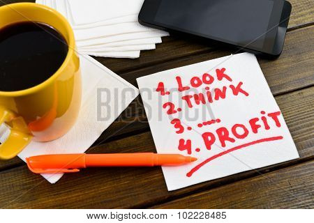 Look think profit writing on white napkin around coffee pen and phone on wooden table