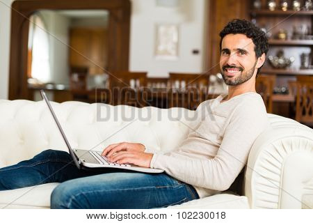Man using a laptop while sitting on the couch in his apartment's living room