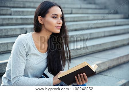 Portrait of a charming young woman sitting on the city stairs with book outdoors