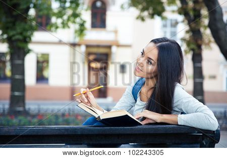 Portrait of a thoughtful female student sitting on the bench with book and pencil outdoors