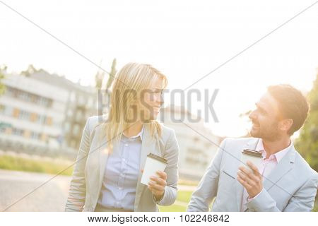Happy business couple conversing while holding disposable cups in city