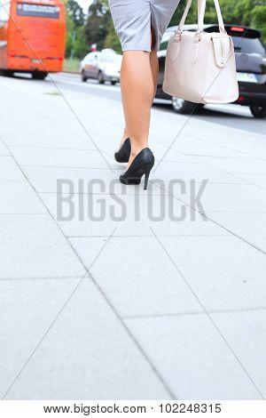 Low section of businesswoman walking on sidewalk