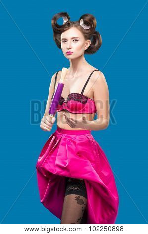 Sexy young housewife standing with a rolling pin in her hand.