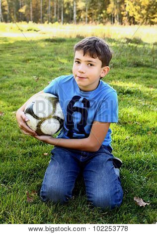 boy with soccer ball on green grass background