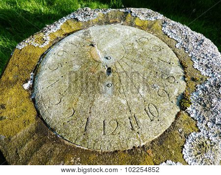 sundial covered with lichen in a churchyard