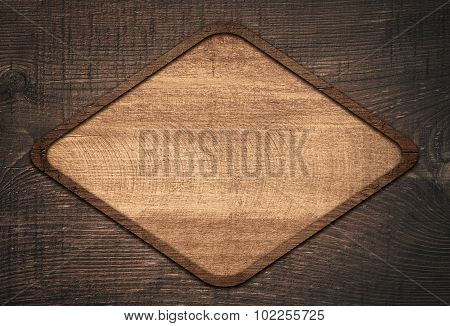 Brown wooden lozenge with frame on dark wall