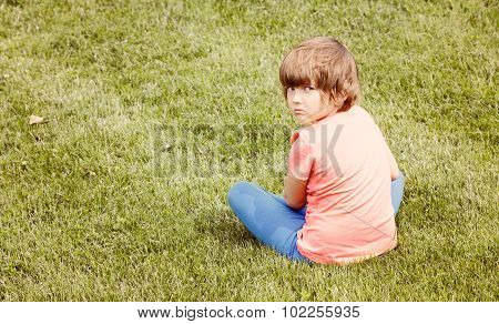 Offended Young Girl Sitting On The Grass