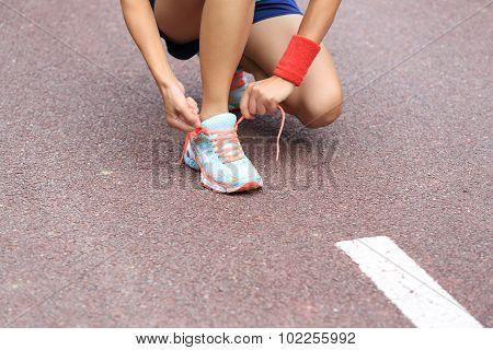 young asian woman runner tying shoelace