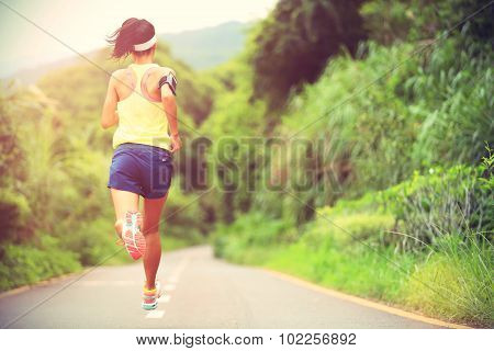 fitness woman trail runner running on forest trail