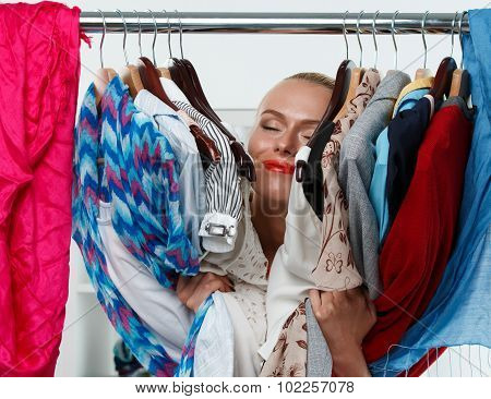 Beautiful Smiling Blonde Woman Standing Inside Wardrobe Rack