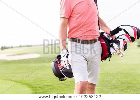 Midsection of man with golf club bag standing at course