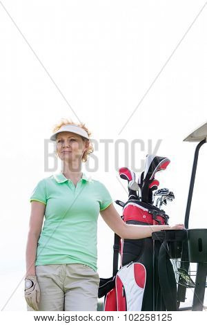 Low angle view of smiling golfer standing against clear sky