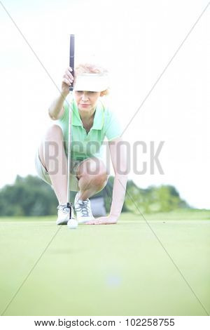 Middle-aged woman aiming ball at golf course