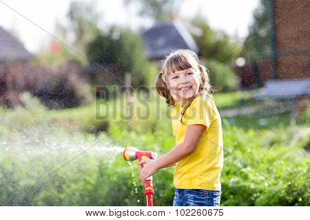 Cheerful child watering plants from hose spray in garden at backyard of house at sunny summertime